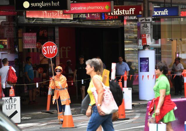 A traffic controller (L) works at a building site in central Sydney on December 7, 2016. Australia's economy contracted for just the fourth quarter in 25 years, official data showed, slowing the annual growth rate to 1.8 percent amid weaker government and consumer spending on top of softer trade figures