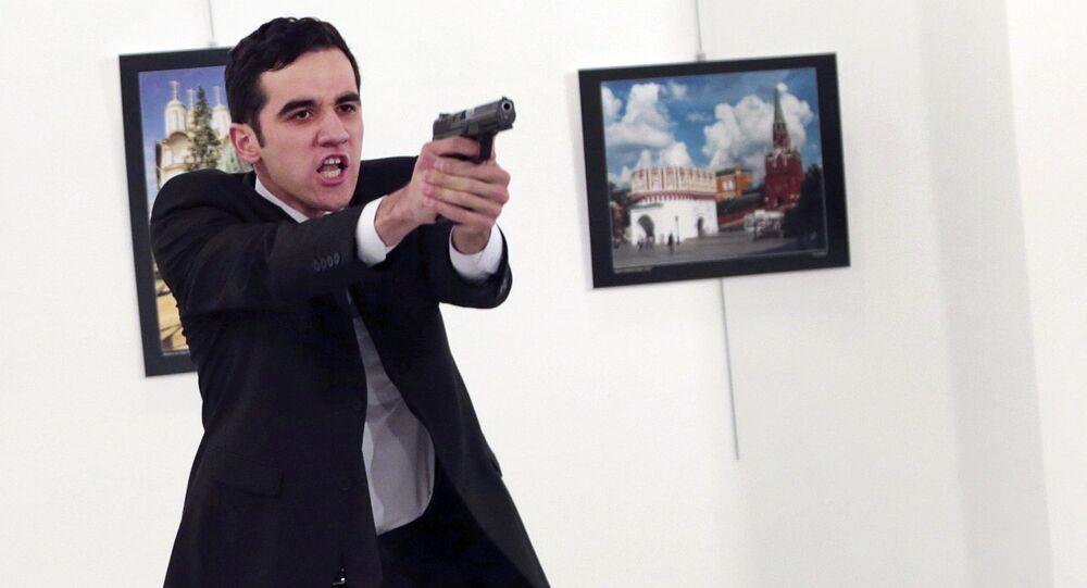Gunman gestures after shooting the Russian Ambassador to Turkey, Andrei Karlov, at a photo gallery in Ankara, Turkey, Monday, Dec. 19, 2016