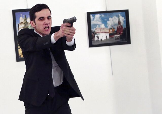 Gunman gestures after shooting the Russian Ambassador to Turkey, Andrei Karlov, at a photo gallery in Ankara, Turkey, Monday, Dec. 19, 2016