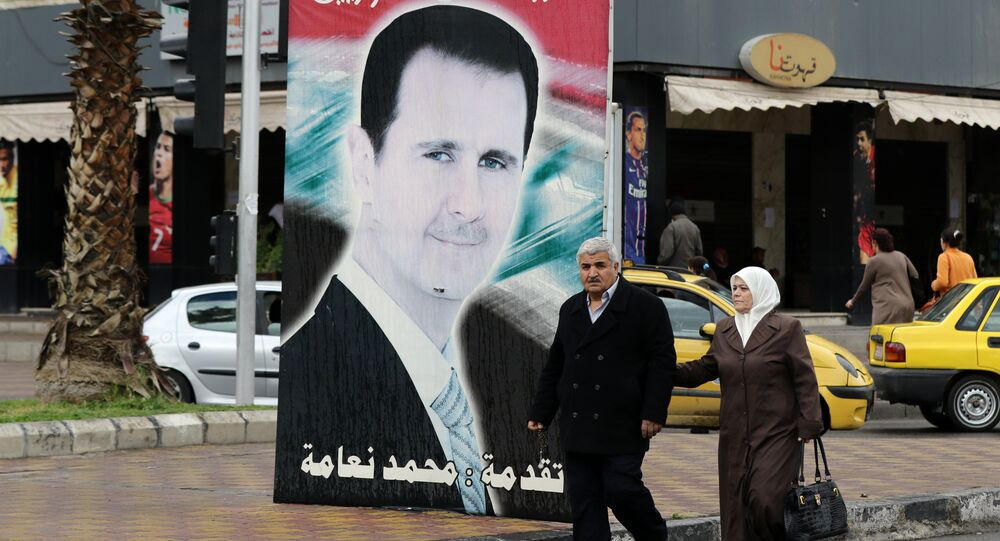 Syrians walk past a portrait of President Bashar al-Assad in the capital Damascus on March 15, 2016
