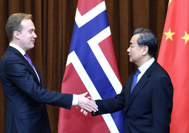 In this photo released by Xinhua News Agency, Chinese Foreign Minister Wang Yi at right shakes hands with Norwegian Foreign Minister Borge Brende in Beijing, capital of China, Monday, Dec. 19, 2016