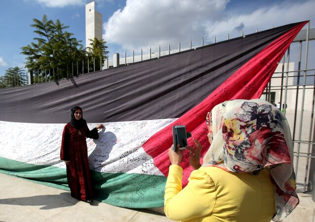A Palestinian woman takes a picture of a 66-meter-long Palestinian flag