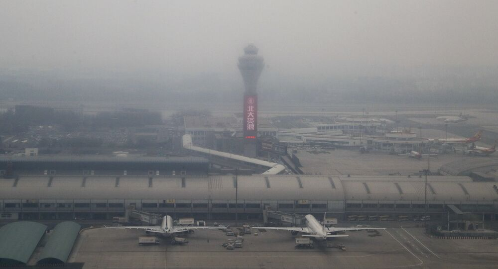 Passenger planes are on the tarmac at the Beijing Capital International Airport shrouded by pollution haze