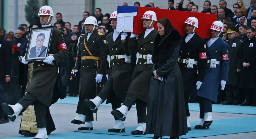 Members of a Turkish forces honour guard carry the Russian flag-draped coffin of Russian Ambassador to Turkey Andrei Karlov who was assassinated Monday, as an officer, left, holds his picture during a ceremony at the airport in Ankara, Turkey, Tuesday, Dec, 20, 2016