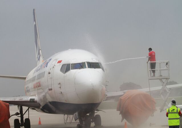 Airport employees wash ash from an airplane at Solo airport in Central Java on February 15, 2014, following the volcanic eruption of Mouth Kelud in East Java on February 13