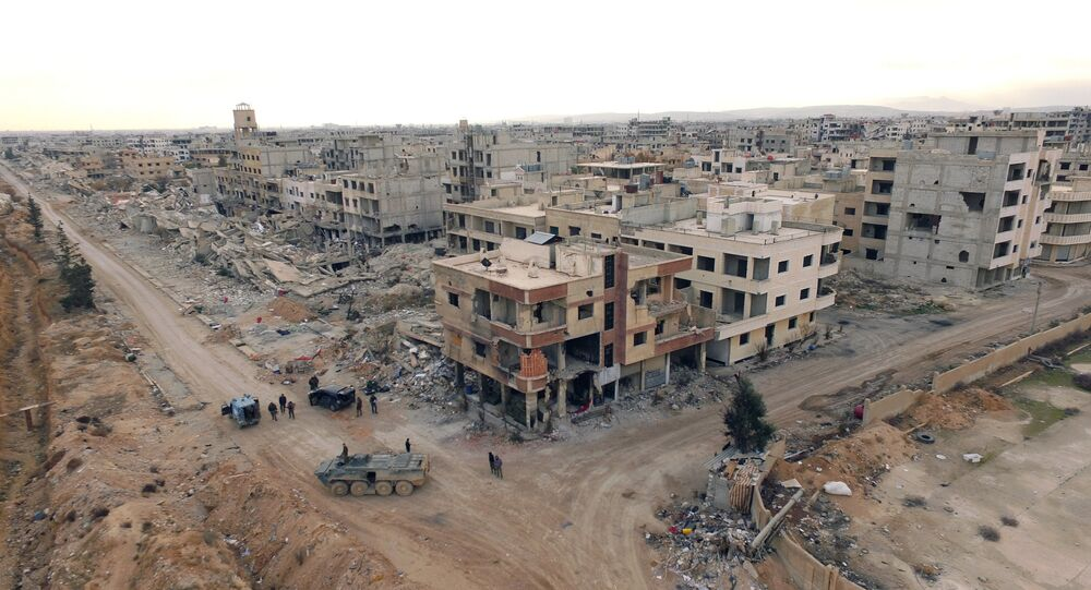 Syrian army troops move through the town of Darayya, a suburb of Damascus.