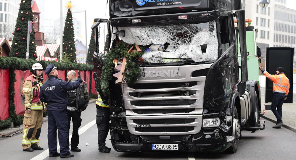A policeman and firemen stand next to a truck on December 20, 2016 at the scene where it crashed into a Christmas market near the Kaiser-Wilhelm-Gedaechtniskirche (Kaiser Wilhelm Memorial Church) in Berlin