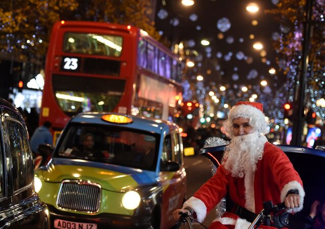 A man dressed as Santa Claus cycles on Oxford Street, which is illuminated with Christmas lights, in London, Britain, December 9, 2016