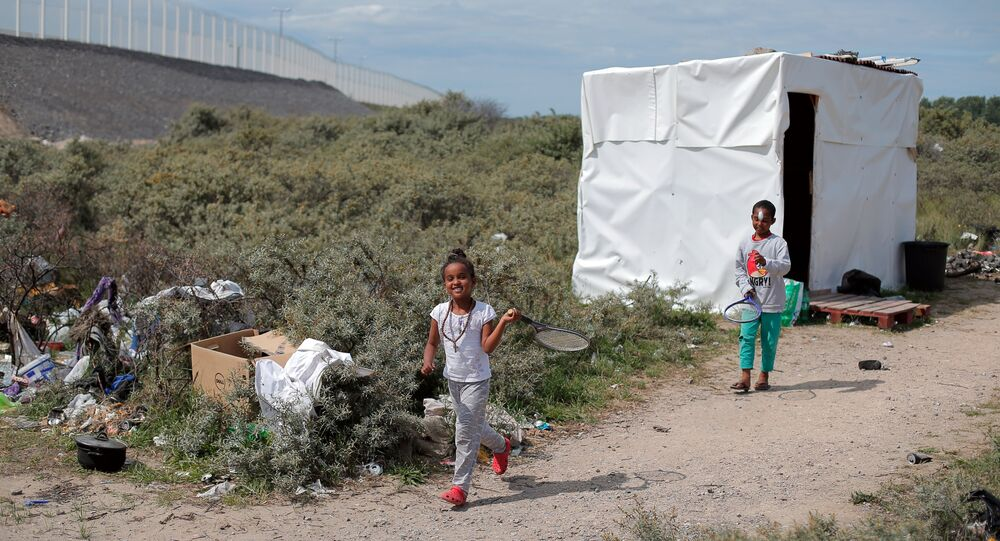 Children play in a makeshift migrant camp known as the Jungle, in Calais, northern France, Wednesday, July 29, 2015
