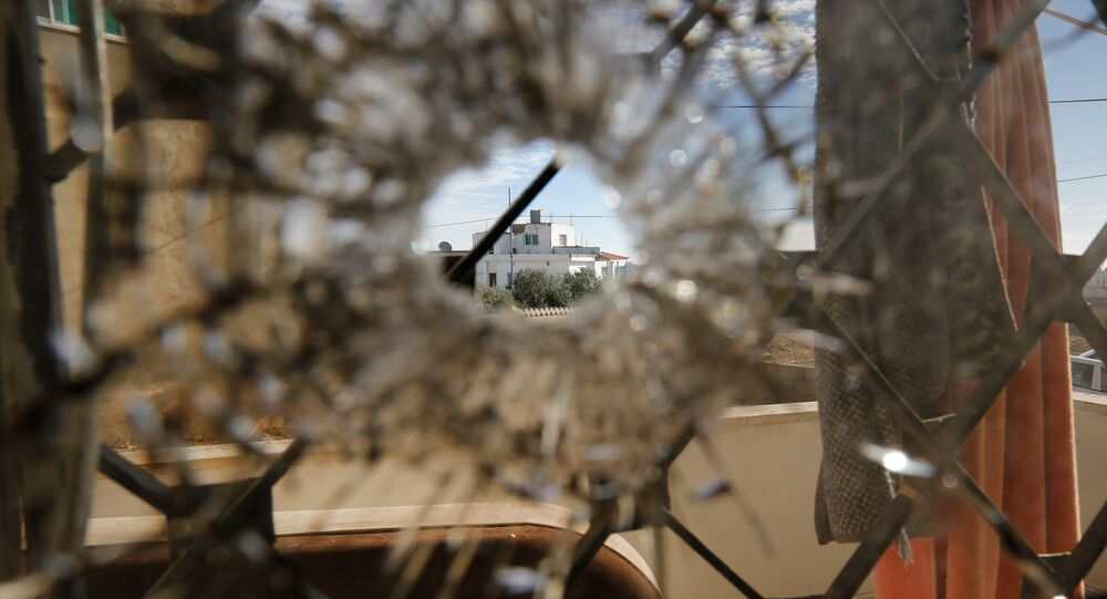 A nearby house is pictured through a bullet hole in a window inside a building that was the site of clashes between Jordanian police and Islamist militant gunmen in the village of Garifla, in Karak, Jordan, December 21, 2016