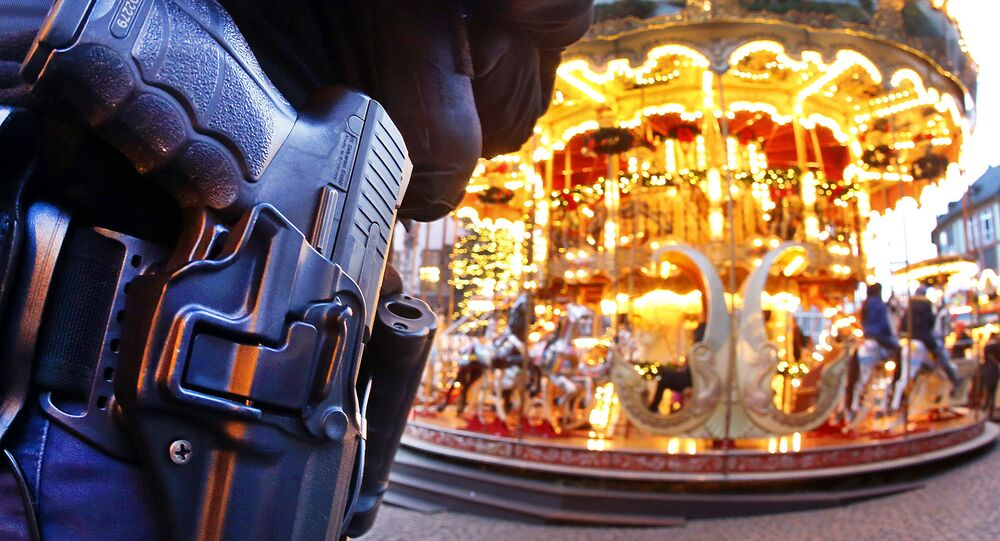 A German police officer stands next to a merry-go-round in the Christmas market in Frankfurt, Germany, Tuesday, Dec. 20, 2016 one day after a truck ran into a crowded Christmas market in Berlin killing several people