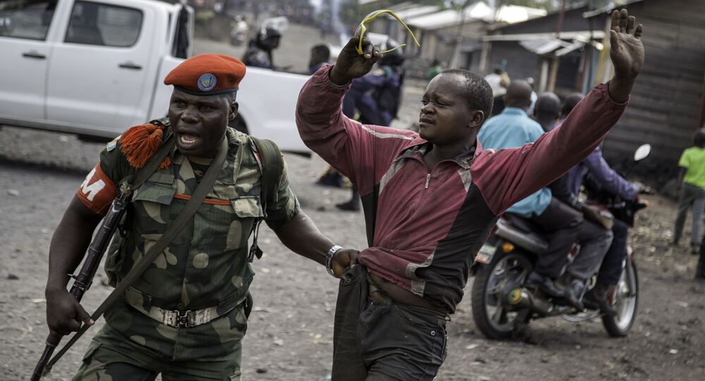 A man is arrested by a member of the military police after people attempted to block the road with rocks,  in the neighbourhood of Majengo in Goma, eastern Democratic Republic of the Congo