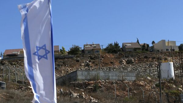 Israeli national flag flying next to an Israeli building site of new housing units in the Jewish settlement of Shilo in the occupied Palestinian West Bank. (File) - Sputnik International