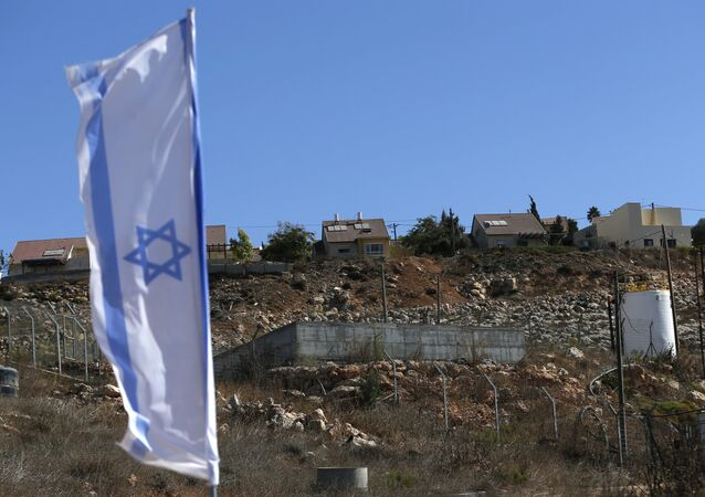 Israeli national flag flying next to an Israeli building site of new housing units in the Jewish settlement of Shilo in the occupied Palestinian West Bank.
