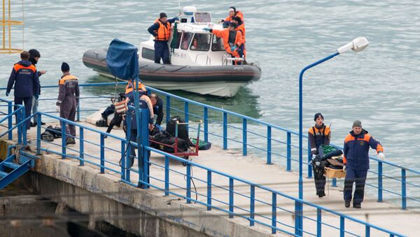 Russian rescuers carry a stretcher with passenger belongings after a Russian military plane crashed in the Black Sea, on a pier outside Sochi - Sputnik International