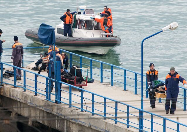 Russian rescuers carry a stretcher with passenger belongings after a Russian military plane crashed in the Black Sea, on a pier outside Sochi
