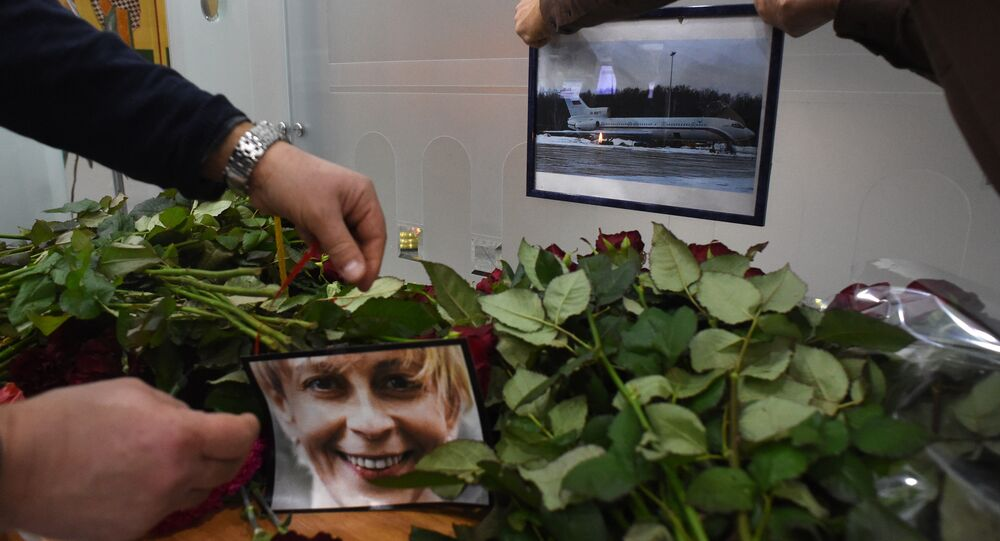 People place a portrait of the founder of Voters' League, charity activist Elizaveta Glinka, known as Dr Liza and a picture of the TU-154 airplane at the airport of the city of Sochi on December 25, 2016, after a Russian military plane which carried dozens of Red Army Choir members crashed. The Russian military