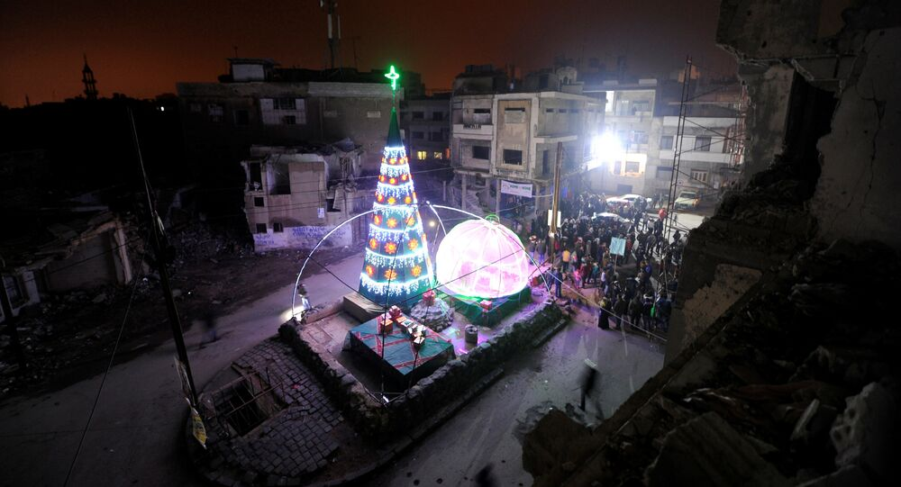 People gather by a Christmas tree near damaged buildings during Christmas eve in al-Hamidiyah neighbourhood in the old city of Homs, Syria December 24, 2016