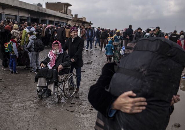A man in a wheelchair waits to be transferred to a camp for internally displaced people, in Bartella, around 30 km (19 miles), from Mosul, Iraq, Monday, Dec. 26, 2016