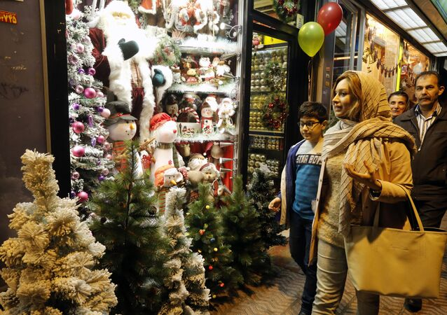 Iranians walk past Christmas decoration at a shop in the capital Tehran on December 24, 2016, on Christmas eve