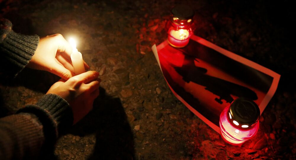 A woman places a candle to honour passengers and crew members of Russian military Tu-154 plane crashed into the Black Sea on its way to Syria on Sunday, at an embankmen in the resort city of Sochi, Russia December 25, 2016
