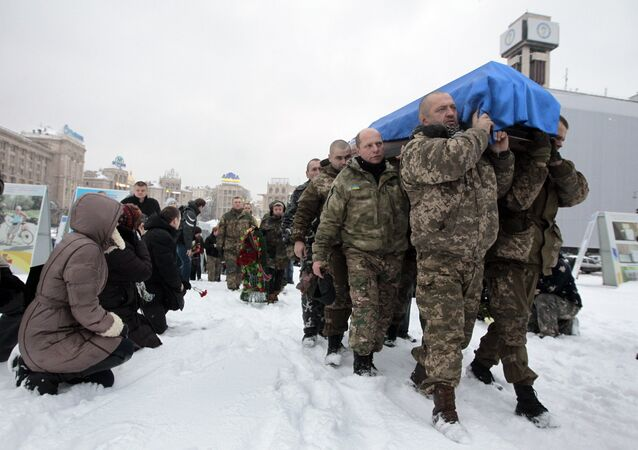 People, including servicemen and civilians, stand and kneel as the Ukrainian soldiers carry the coffin bearing the body of police captain Oleksandr Ilnitsky, who was shot dead by a sniper in the war conflict-hit Donetsk region, during a commemoration ceremony in Independence Square in Kiev, Ukraine, on Monday, Jan. 11, 2016