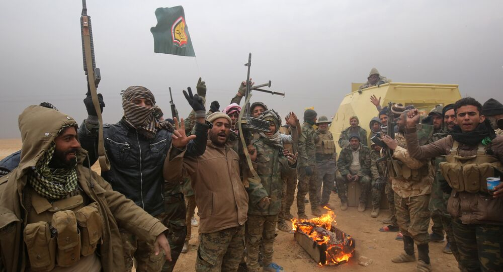 Iraqi Shiite fighters from the Hashed al-Shaabi (Popular Mobilisation) paramilitaries gesture to the camera as they warm up around a fire near the village of Tal Faris, south of Tal Afar, on November 30, 2016, during a broad offencive by Iraq forces to retake the city Mosul from jihadists of the Islamic State group