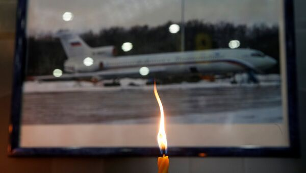 A candle is placed in front of a picture of Tu-154 plane, to commemorate passengers and crew members of Russian military plane, which crashed into the Black Sea on its way to Syria on Sunday, at the Sochi International Airport (Sochi-Adler Airport) in the Black Sea resort city of Sochi, Russia, December 26, 2016 - Sputnik International