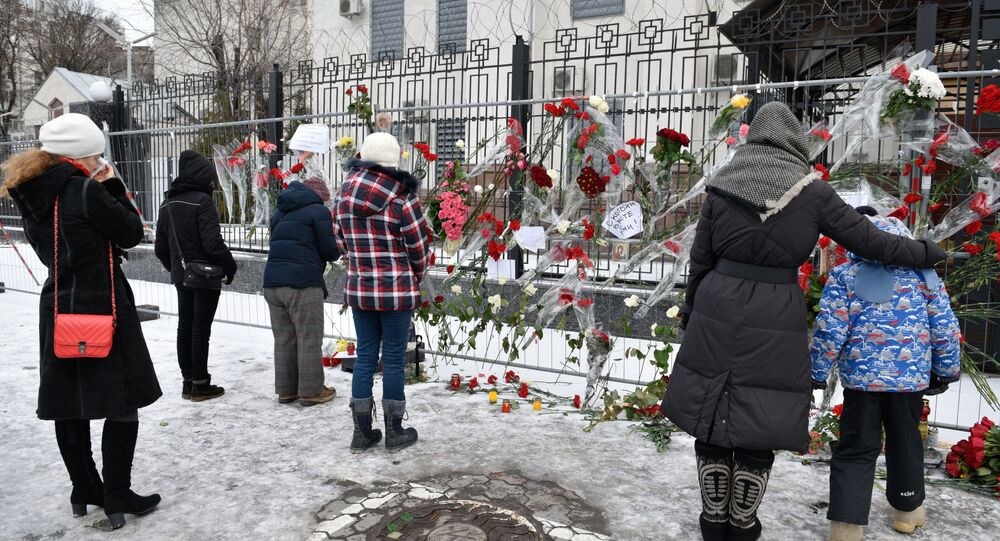 Kiev residents stand at the Russian Embassy in Kiev after laying flowers in memory of the TU-154 air crash victims in Sochi