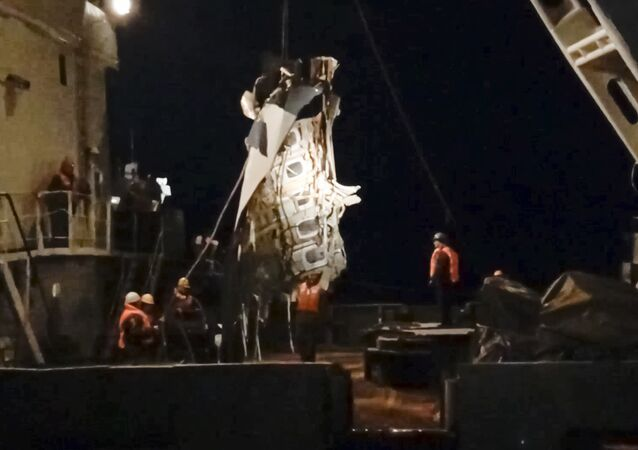 In this late Monday, Dec. 26, 2016 frame grab image provided by the Russian Emergency Situations Ministry Press Service, ministry employees lift a fragment of a plane in the Black Sea, outside Sochi, Russia