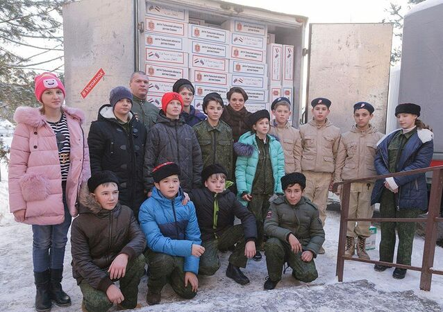 Students in Tula pose for a photo in front of over 500 boxes of gifts for children in Syria