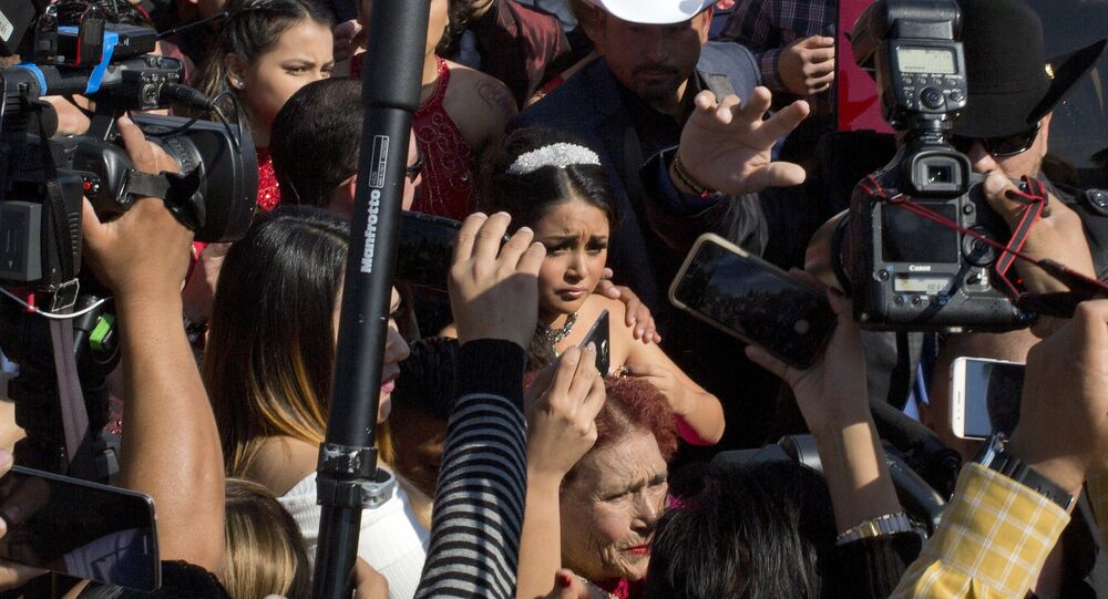 Rubi Ibarra arrives at the site of a Mass that is part of her down-home 15th birthday party, surrounded by a horde of journalists, in the village of La Joya, San Luis Potosi State, Mexico, Monday, Dec. 26, 2016