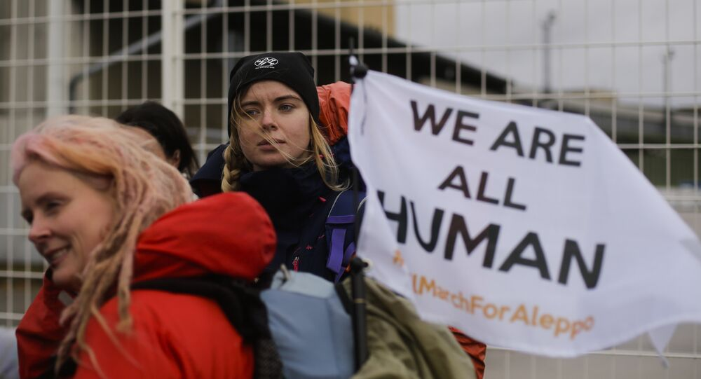 Demonstrators wait for the launch of the Civil March for Aleppo at the air field of the former airport Tempelhof in Berlin, Monday, Dec. 26, 2016