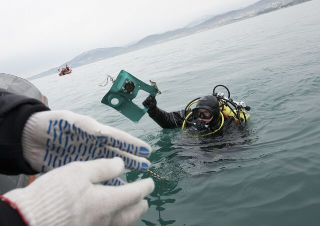 A Russian Emergency Ministry diver lifts a fragment of a plane in the Black Sea, outside Sochi, Russia, Tuesday, Dec. 27, 2016