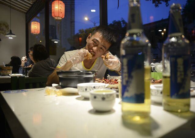 This picture taken on September 8, 2016 shows a man eating a rabbit head at a restaurant in Chengdu, in southwestern China's Sichuan province