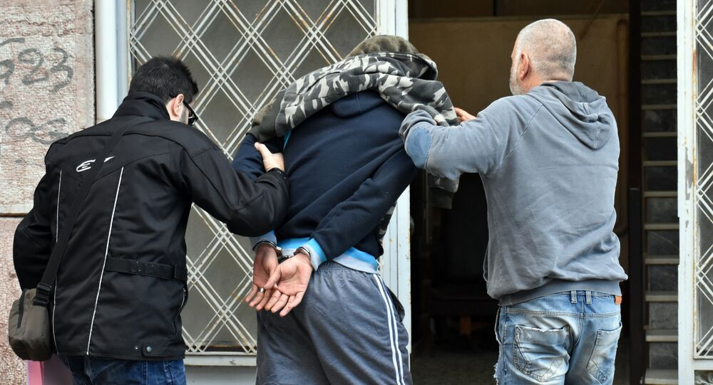 A Syrian man is escorted by police officers before a prosecutor on the island of Chios on December 14, 2016 after being suspected of brutally beating a three-year-old refugee boy in a camp shower