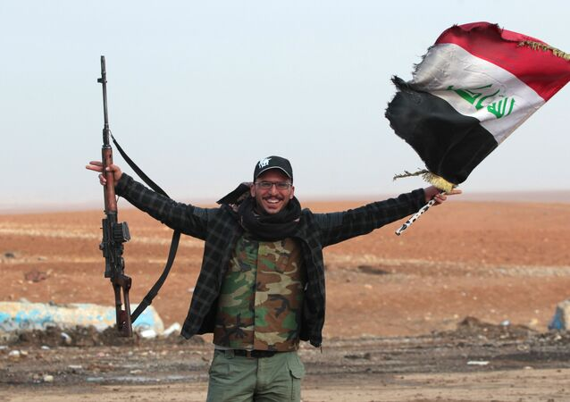 An Iraqi forces member flashes his gun as he waves his national flag in the village of Arabat, south of Mosul, as temperatures continue to drop, on December 1, 2016