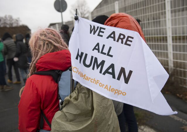 A participant's flag reading 'We are all human' is fixed at a backpack during a solidarity march for Aleppo in Berlin, Germany, on December 26, 2016