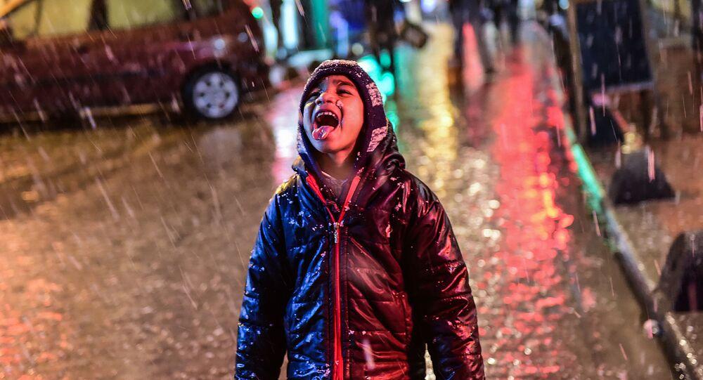 Сирийский мальчик радуется снегу на улице Стамбула