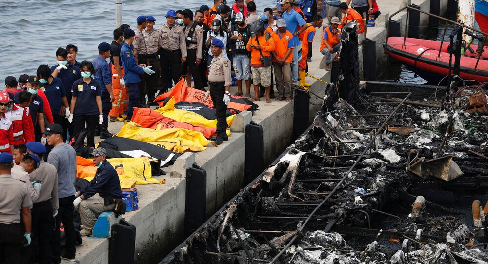 Police, Red Cross and rescue workers prepare to remove body bags containing the remains of victims after a fire ripped through a boat carrying tourists to islands north of the capital, at Muara Angke port in Jakarta, Indonesia January 1, 2017.