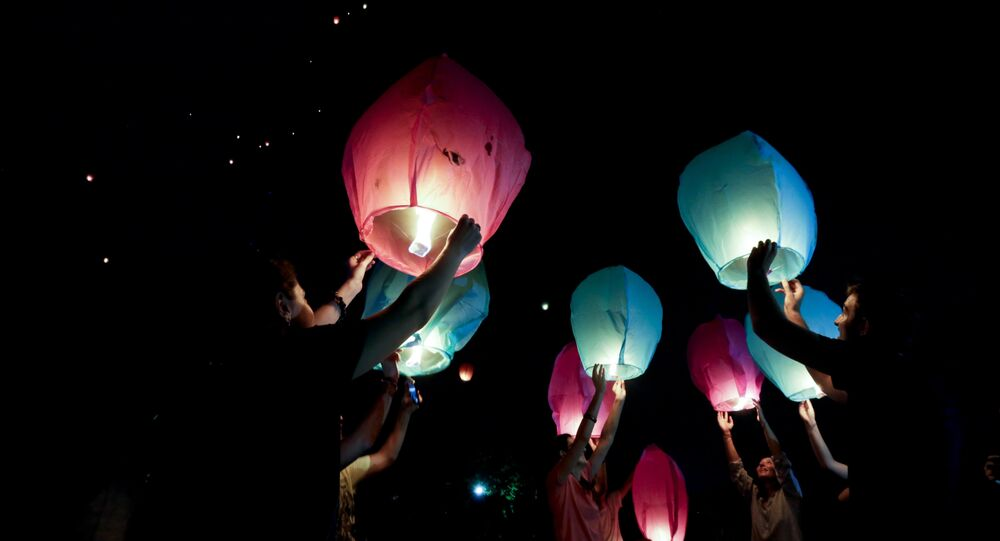People hold sky lanterns to release during a campaign against the use of firecrackers during Diwali festival in Kolkata, India