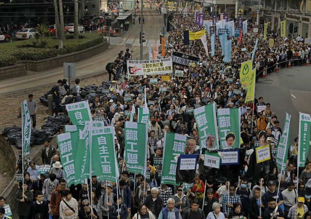 Thousands of people march on the first day of 2017 at a downtown street in Hong Kong Sunday, Jan. 1, 2017, to protest against Beijing's interpretation of Basic Law and Hong Kong government's bid to ban pro-democracy lawmakers from taking office. They also demand true universal suffrage, which is not happening in the coming chief executive election in March.