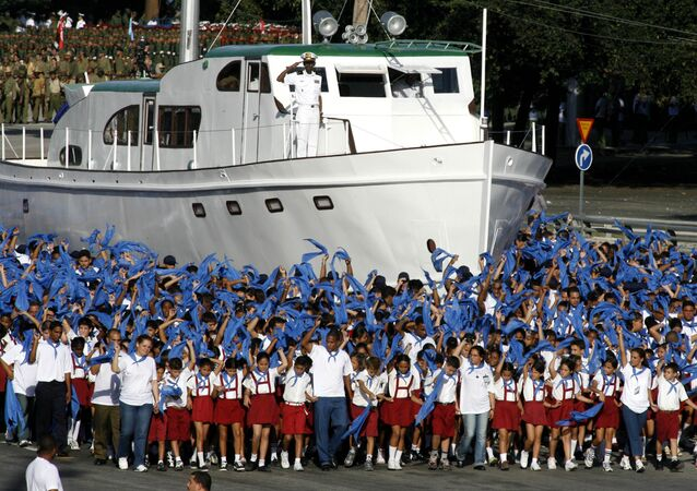 Cuban children march next to a replica of the Granma boat during a military parade along the Revolution Square in Havana,Cuba,Saturday,Dec.2,2006.