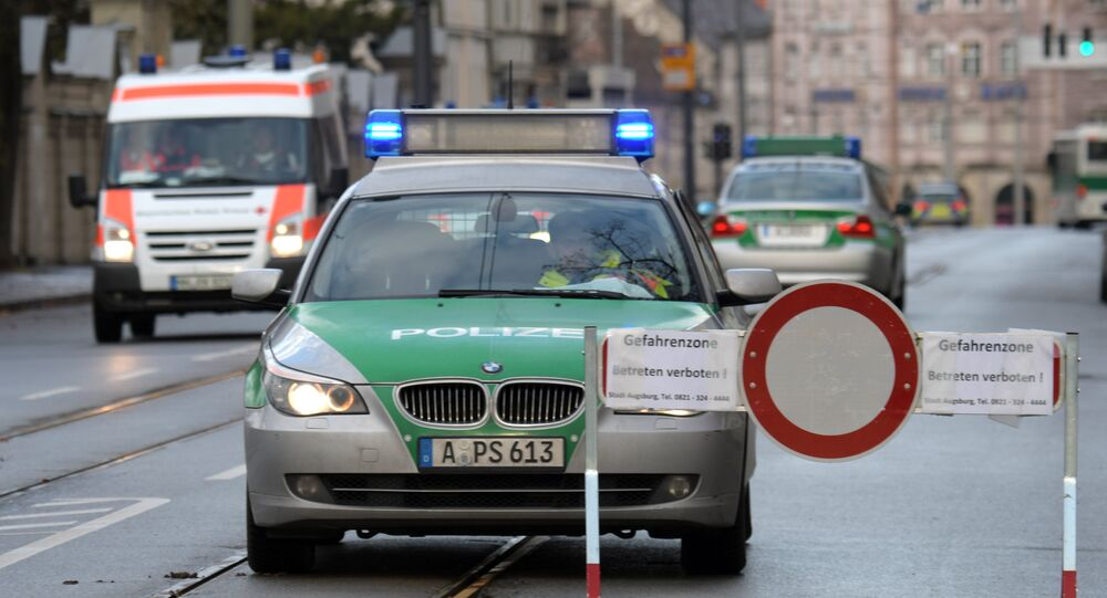 Police cars are seen beside a road block on an empty street in Augsburg, southern Germany