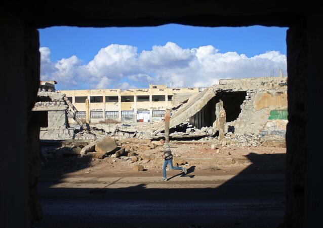 A Syrian boy runs past the rubble of destroyed buildings in the rebel-held area of Daraa, in southern Syria, on January 1, 2017