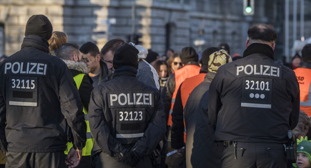 German police officers watch over a security check near the capital's Brandenburg Gate on December 31, 2016, as revellers arrive for New Year celebrations
