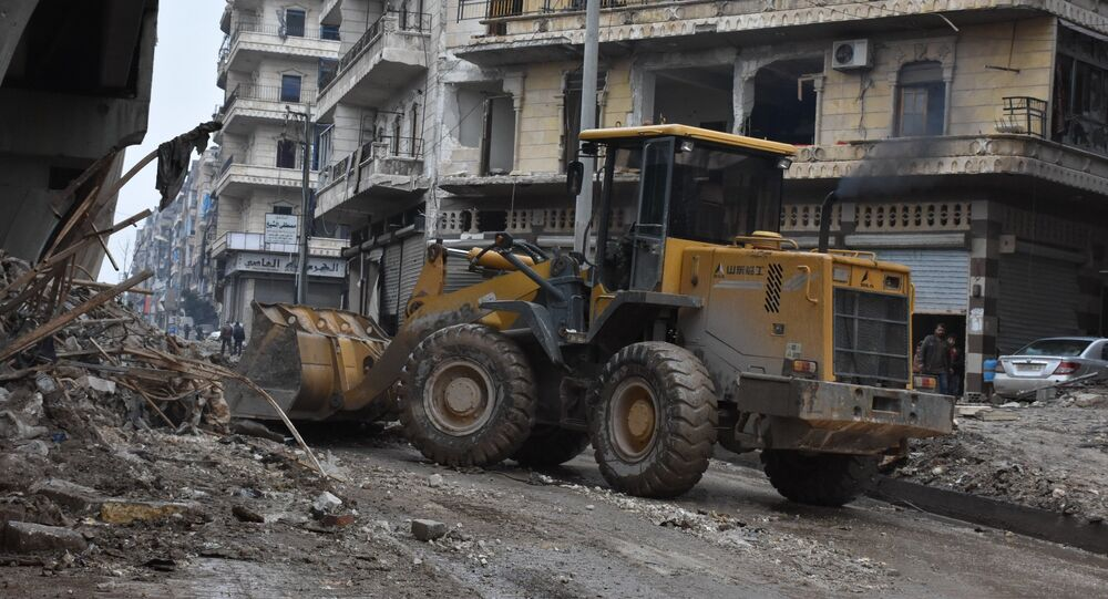 Tractors are seen as the Syrian government starts to clean up areas formerly held by opposition forces in the northern city of Aleppo on December 27, 2016