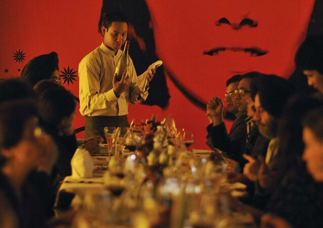 In this Sunday, Jan. 16, 2011 photo, a waiter serves wine to a group learning wine appreciation and fine dining, being conducted by Tulleeho Beverage Innovations at a restaurant in New Delhi, India