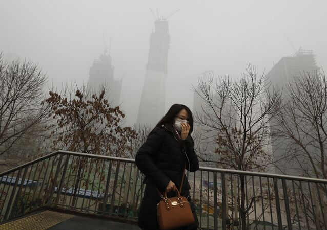 A woman wearing a mask for protection against air pollution walks on a pedestrian overhead bridge in Beijing as the capital of China is shrouded by heavy smog on Tuesday, Dec. 20, 2016