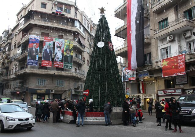 Syrians gather around a Christmas tree in Aleppo's government controlled Aziziyah neighbourhood on December 31, 2016